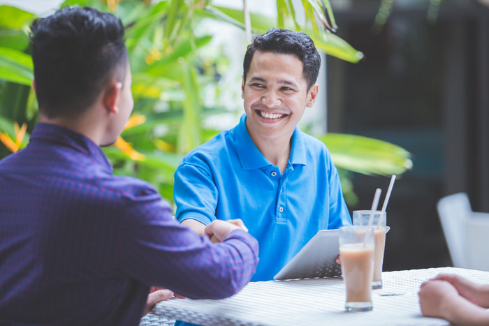 portrait two asian Business people shake hand coffee shop
